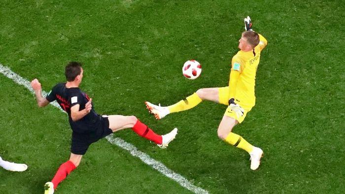 Inggris memang tersingkir oleh Kroasia di semifinal, tapi kipernya layak masuk 11 pemain terbaik di babak ini. Jordan Pickford melakukan lima penyelamatan termasuk saat menghalau tendangan jarak dekat Mario Mandzukic ini. Tapi buruknya pertahanan Inggris secara keseluruhan membuat gawangnya kebobolan dua kali. (Foto: Kai Pfaffenbach/REUTERS)