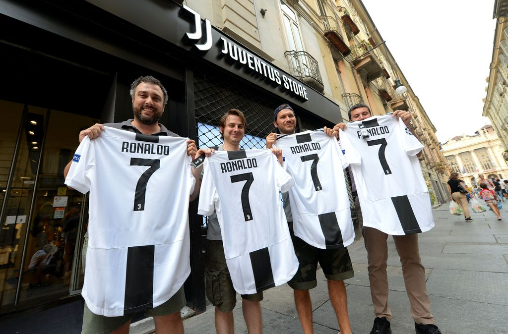 Juventus supporters hold, after buying, the original Juventus' jersey printed with the name and number of Cristiano Ronaldo after his transfer to Juventus in Turin, Italy July 10, 2018. REUTERS/Massimo Pinca