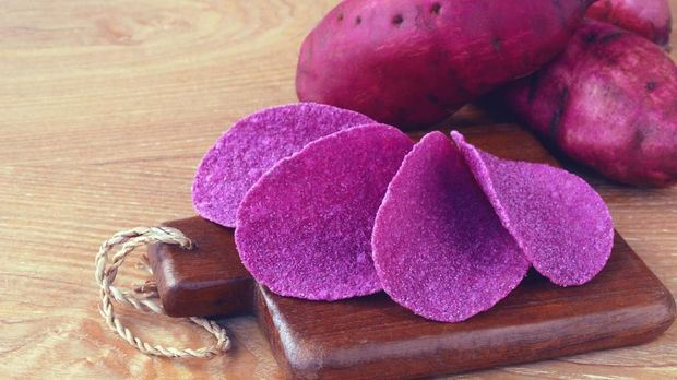 potato chips with raw sweet potatoes root in purple skin on wooden background