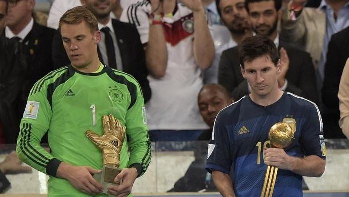 Lionel Messi berhak atas Bola Emas Piala Dunia 2014 dan menerimanya di samping kiper Jerman Manuel Neuer yang dapat Sarung Tangan Emas. Messi tampak tak puas cuma jadi pemain terbaik turnamen karena Argentina dikalahkan Jerman di final. (Foto: Juan Mabromata/AFP)