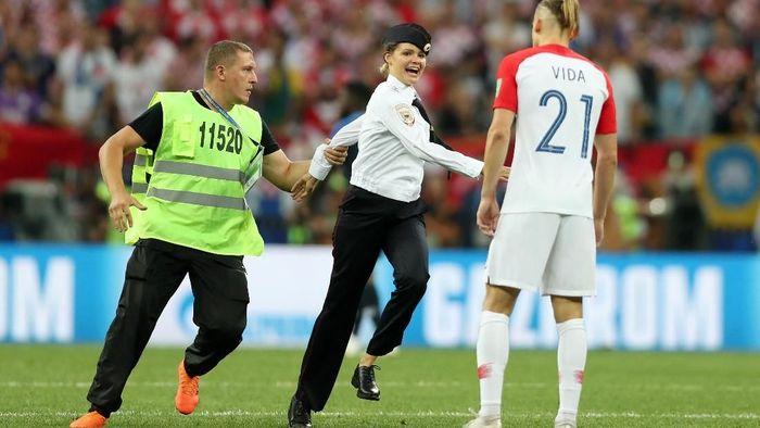 Anggota Pussy Riot saat menerobos pertandingan final Piala Dunia 2018 antara Prancis vs Kroasia di Luzhniki Stadium, Moskow, Minggu (15/7). (Foto: Clive Rose/Getty Images)