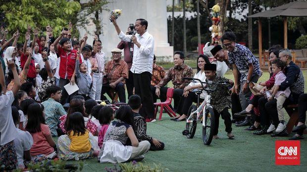 Presiden Jokowi menghadiahkan sepeda kepada seorang anak yang sukses menjawab pertanyaannya, di halaman Istana Merdeka, Jakarta, 20 Juli 2018.