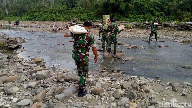 Anggota TNI menyalurkan bantuan untuk suku Mausu Ane yang ada di pedalaman Maluku Tengah.