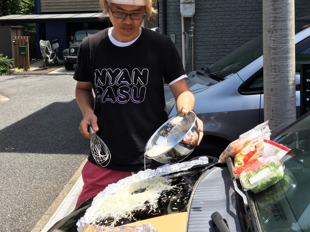 Cuaca Sangat Terik di Jepang, Pria Ini Masak di Kap Mobilnya