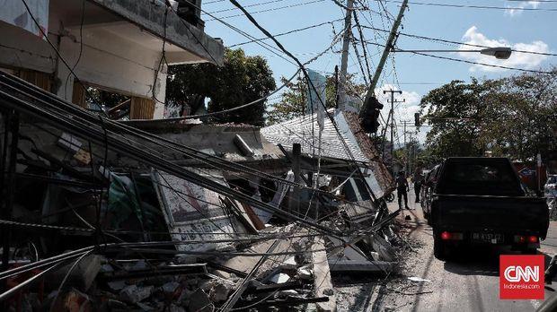 Rumah dan tiang listrik roboh akibat gempa Lombok.