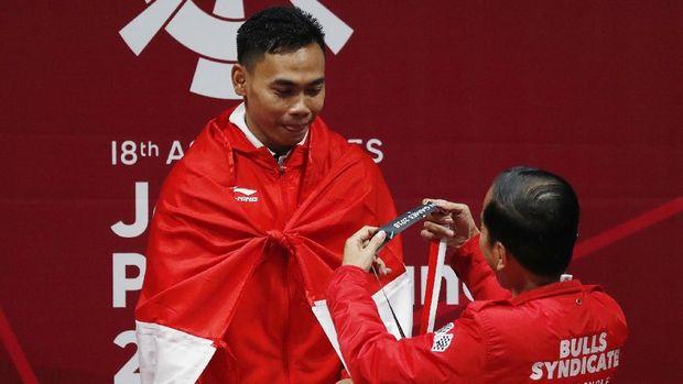 Presiden Jokowi mengalungkan medali emas Asian Games 2018 kepada Eko Yuli.