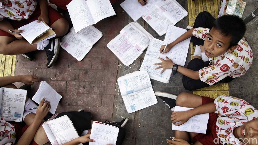 Patut Dicontoh! Siswa SD Ini Menunggu Bus Sambil Belajar