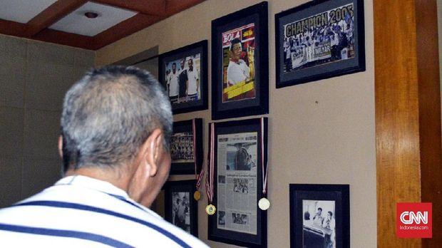 Benny Dolo menatap sejumlah foto semasa aktif sebagai pemain dan pelatih.