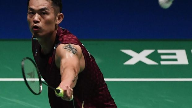China's Lin Dan hits a return towards Japan's Kento Momota during their men's singles quarter-final match at the Japan Open badminton championships in Tokyo on September 14, 2018. / AFP PHOTO / Toshifumi KITAMURA