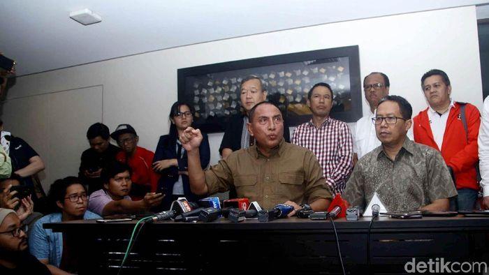 Anggota exco PSSI Johar Lin Eng (baju hitam) berdiri di belakang Ketum PSSI Edy Rahmayadi saat mengumumkan penghentian Liga 1 beberapa waktu lalu. (Pradita Utama/detikSport)