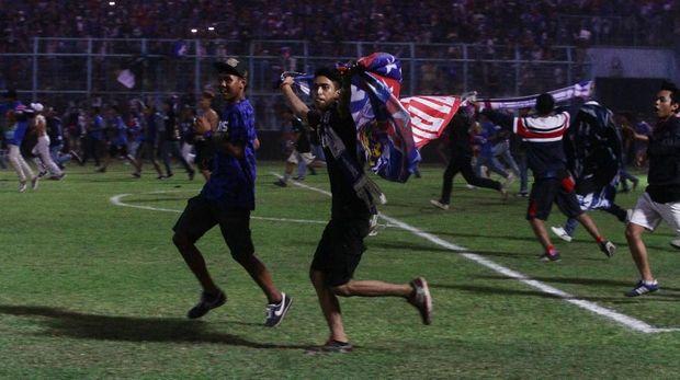 Suporter Arema memasuki lapangan saat tim kesayangannya mengalahkan Persebaya 1-0.