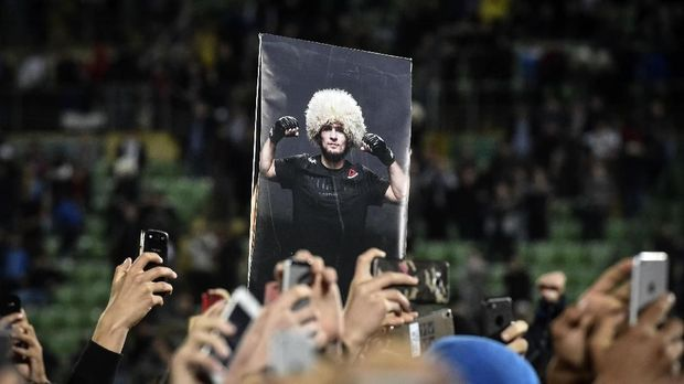 Fans hold a picture of UFC lightweight champion Khabib Nurmagomedov of Russia during a meeting upon the arrival at the Anzhi-arena stadium in Makhachkala on October 8, 2018.He defeated Conor McGregor of Ireland in their UFC lightweight championship bout by way of submission during the UFC 229 event inside T-Mobile Arena on October 6, 2018 in Las Vegas, Nevada / AFP PHOTO / Vasily MAXIMOV