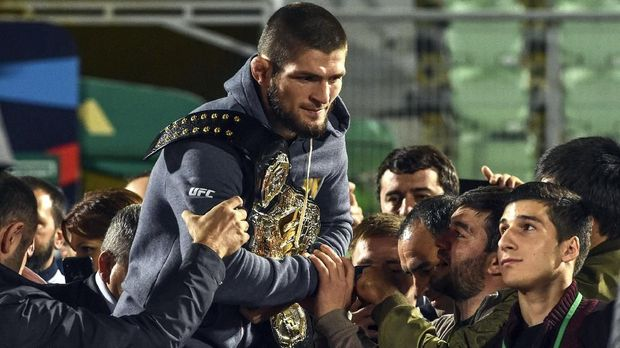 UFC lightweight champion Khabib Nurmagomedov of Russia carries his champions belt as he is escorted by fans upon the arrival in Makhachkala on October 8, 2018. Nurmagomedov defeated Conor McGregor of Ireland in their UFC lightweight championship bout by way of submission during the UFC 229 event inside T-Mobile Arena on October 6, 2018 in Las Vegas, Nevada. / AFP PHOTO / Vasily MAXIMOV