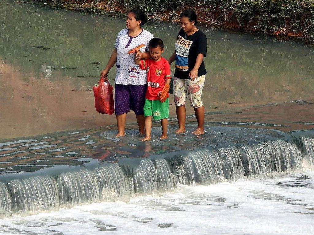 Potret Warga Nekat Sebrangi Kanal Banjir Timur