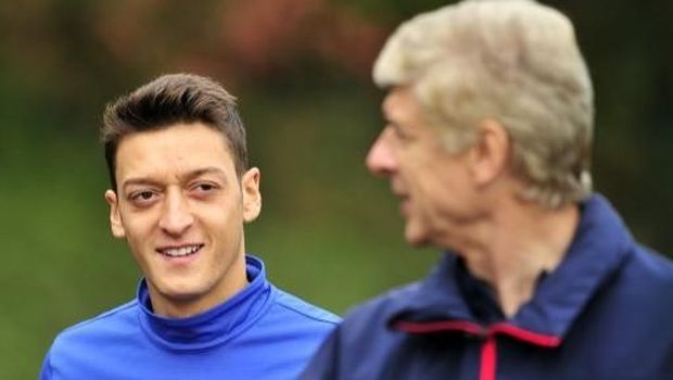 Arsenal's German midfielder Mesut Ozil (L) and French manager Arsene Wenger (R) speak during a team training session for the forthcoming UEFA Champions League Group F football match against SSC Napoli at Arsenal's London Colney training ground in north London on September 30, 2013. Arsenal will play against Napoli at the Emirates Stadium on October 1, 2013. AFP PHOTO/GLYN KIRK (Photo by GLYN KIRK / AFP)