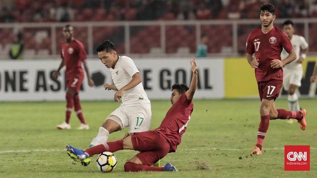 Pesepak bola timnas Indonesia U-19 Syahrian Abimanyu berebut bola dengan pesebak bola Qatar U-19 (merah) pada laga Grup A Piala Asia U-19 2018 di Stadion Utama Gelora Bung Karno, Jakarta (21/10). (CNN Indonesia/Hesti Rika)
