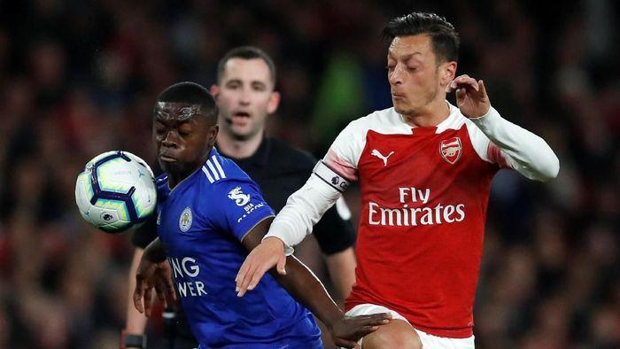 Sebagai gelandang serang, Oezil menjadi otak dari serangan Arsenal saat menghadapi Leicester City. Tampak ia berduel dengan Nampalys Mendy di laga dini hari tadi. (Foto: Andrew Boyers/Reuters)