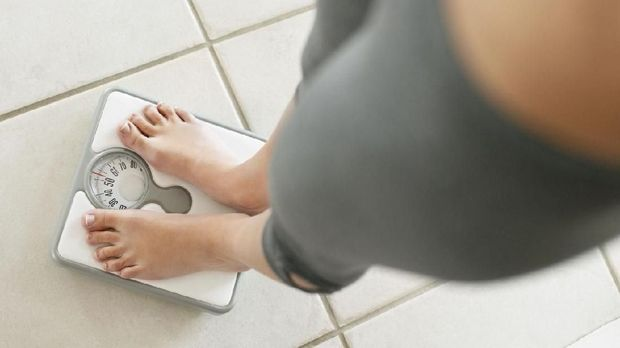 Weighloss- Low section of a young on a weighing scale