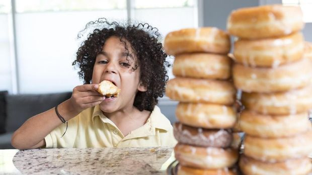 A little boy eats a donut and looks at the camera.  He has a huge pile of donuts in front of him.  He is hispanic and has big natural hair.  He is sitting at a kitchen counter inside a home.