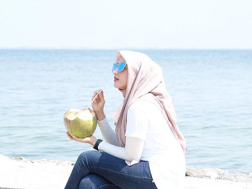 Cantiknya Dokter Nadia Alaydrus Saat Minum Es Kelapa di Pinggir Pantai