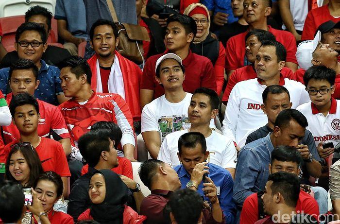 Kaesang menyaksikan laga perdana Grup B Piala AFF 2018 antara Indonesia vs Singapura di National Stadium, Jumat (9/11) malam. Dia hadir dengan mengenakan kaos dan topi warna putih.
