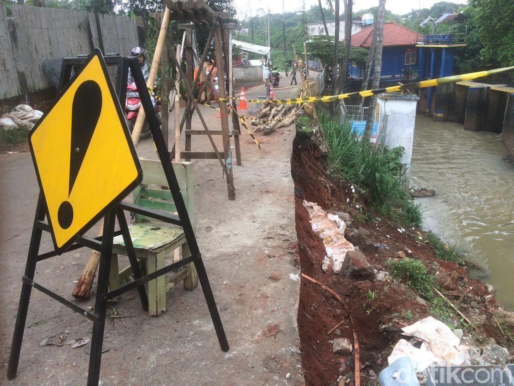 Petugas Perbaiki Jalan Longsor di Setu Cipayung Arah Bekasi
