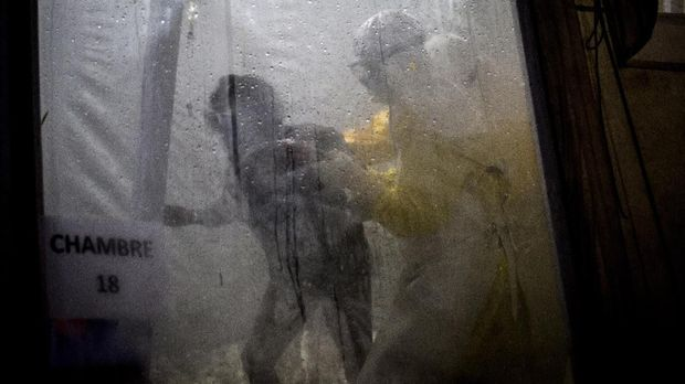Health workers help an unconfirmed Ebola patient into her bed inside a MSF (Doctors Without Borders) supported Ebola Treatment Centre (ETC) on November 3, 2018 in Butembo, Democratic Republic of the Congo. - The death toll from an Ebola outbreak in eastern Democratic Republic of Congo has risen to more than 200, the health ministry said on November 10, 2018. (Photo by John WESSELS / AFP)