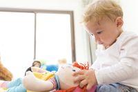 Ilustrasi anak laki-laki main boneka