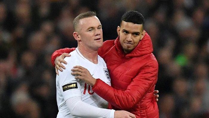 Di pertengahan babak kedua, seorang fans nekat masuk ke dalam lapangan. Dia memeluk Rooney dan langngsung keluar lapangan selepas itu. (Foto: Toby Melville/Reuters)