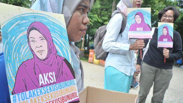 Peserta aksi menunjukkan poster dan kotak donasi pada aksi Tolak Eksekusi Baiq Nuril Maknun di Taman Kamabang Iwak Palembang, Minggu (18/11).