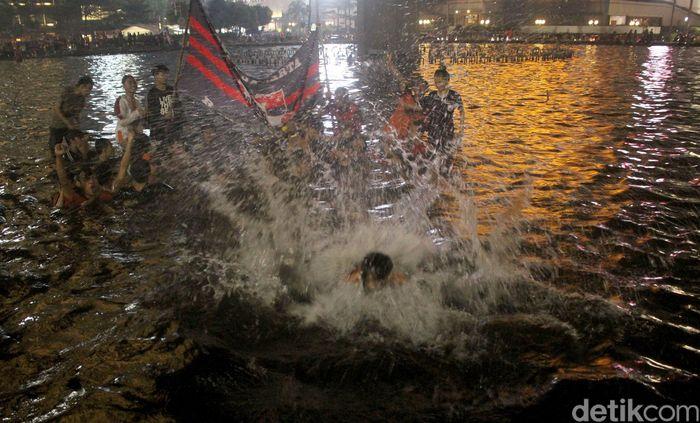 Beberapa supporter yang ikut berpesta menyeburkan diri ke dalam kolam Bunderan Hotel Indonesia.