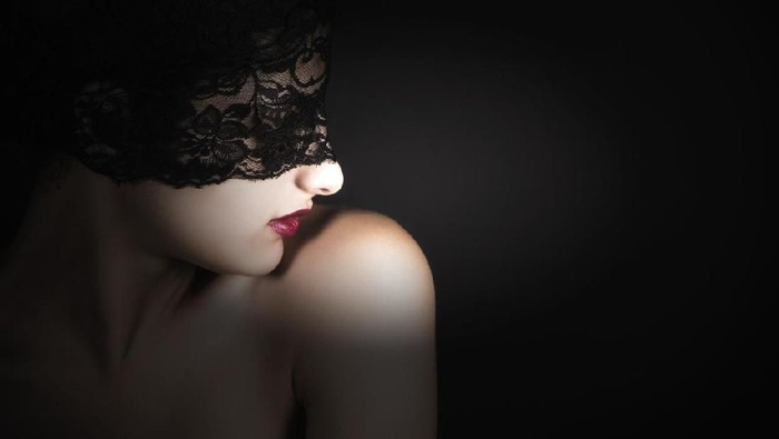 Blindfolded woman with red lip on black background