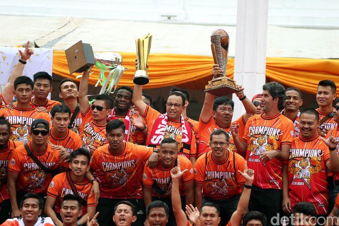 Gubernur DKI Jakarta Anies Baswedan mengangkat tropi Liga 1 saat menerima rombongan Persija.