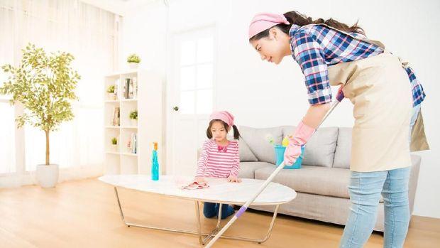 mum teaching daughter cleaning home
