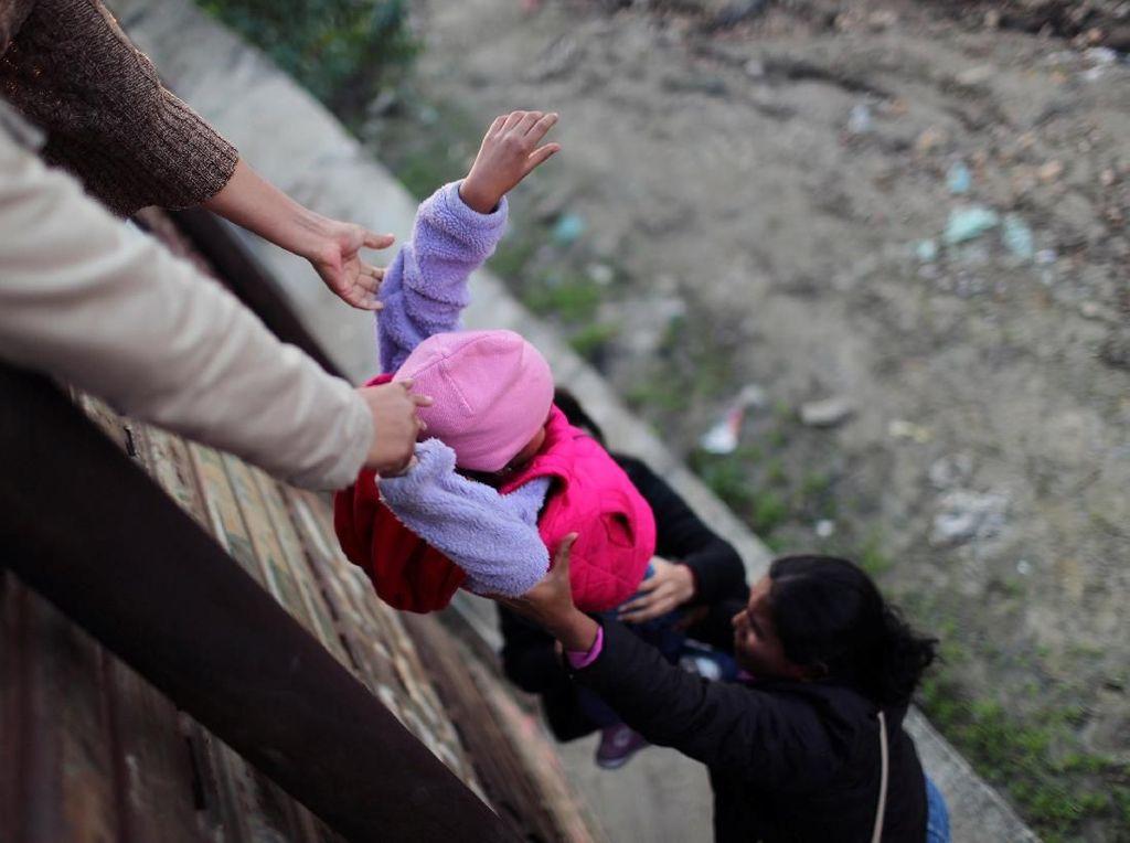 Imigran Honduras Susah Payah Lewati Tembok Perbatasan AS