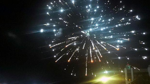 Warna-warni kembang api menyinari langit Makassar.