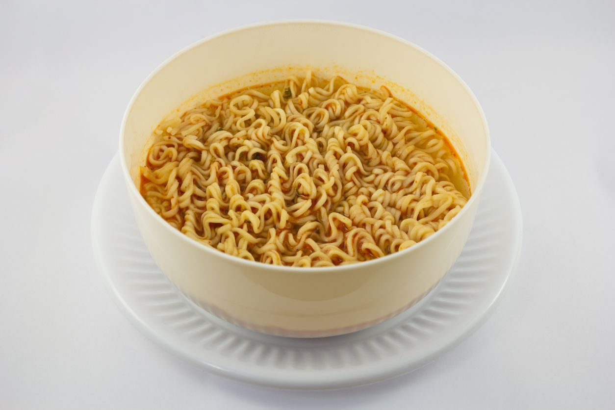 Instant noodle and spicy seasoning in white bowl with chopstick