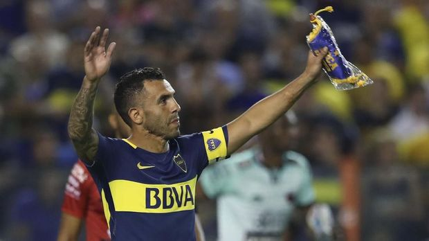 Boca Juniors' Carlos Tevez (R) holds up the team standard after their Argentina First Division Superliga football match against Colon at La Bombonera stadium, in Buenos Aires, on January 27, 2018. - Carlos Tevez returned to Boca Juniors after cutting short a spell with Chinese Super League side Shanghai Shenhua. (Photo by Alejandro PAGNI / AFP)