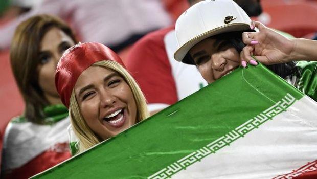 Suporter wanita Iran membentangkan bendera saat menyaksikan Iran vs Yaman di Piala Asia 2019.