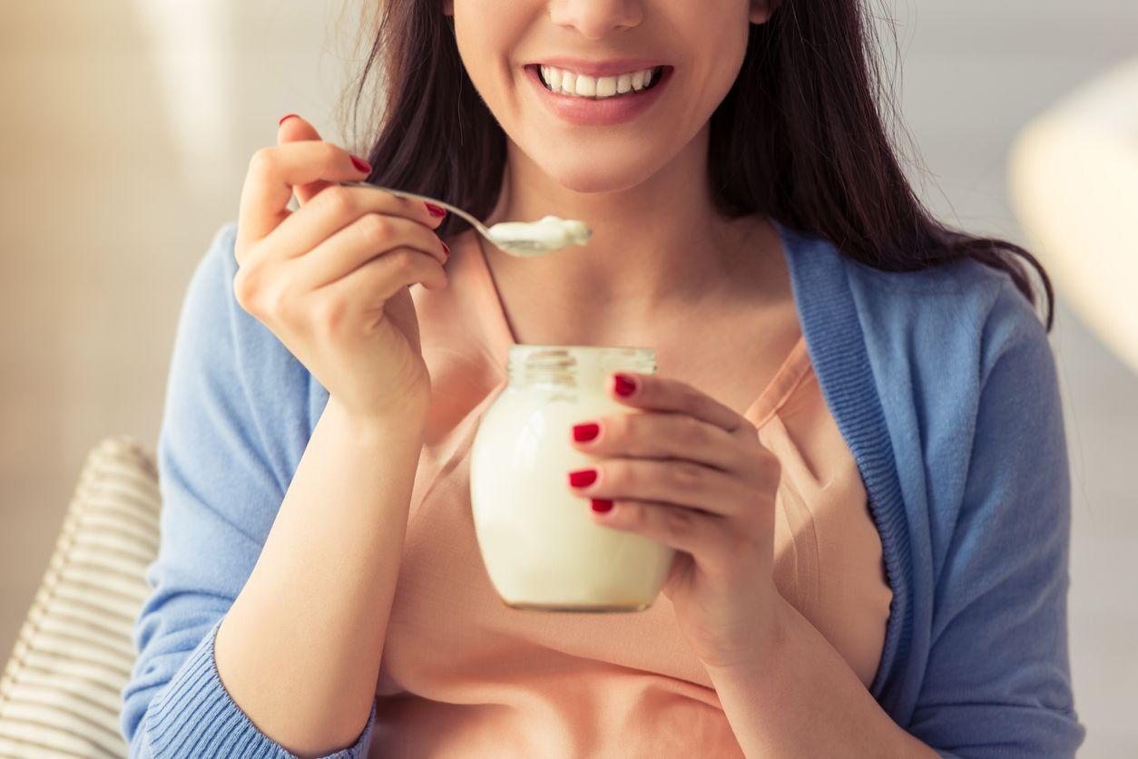 Young woman eating yogurt, closeup