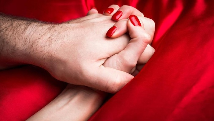 Young female holding hands sensually on red silk bed.