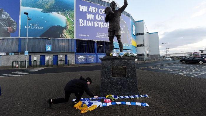 Sala hilang saat terbang dari Nantes ke Cardiff, dan diprediksi pesawatnya jatuh. Duka mulai menyelimuti Cardiff City yang kehilangan pemain barunya itu. Di luar stadion, fans mulai melakukan tribute untuk Sala dengan menaruh syal dan bunga. (Foto: Rebecca Naden/Reuters)