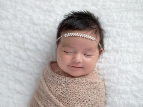 Smiling one month old baby girl swaddled in a beige wrap. Shot in the studio on a white blanket.