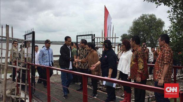Jokowi disambut sejumlah pejabat saat akan memanen udang vaname di Bekasi.