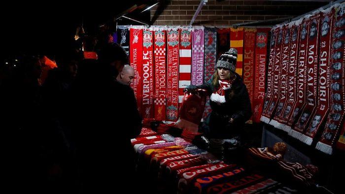 Para pedagang kaki lima di sekitaran Anfield biasanya berjualan jelang pertandingan kandang Liverpool. Anda tertarik membeli pernak-pernik tersebut? (Carl Recine/Reuters)