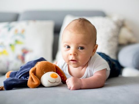 An adorable baby lays on her tummy on a rug in a living room.  She looks up with pursed lips.  There are wooden toys in the foreground.
