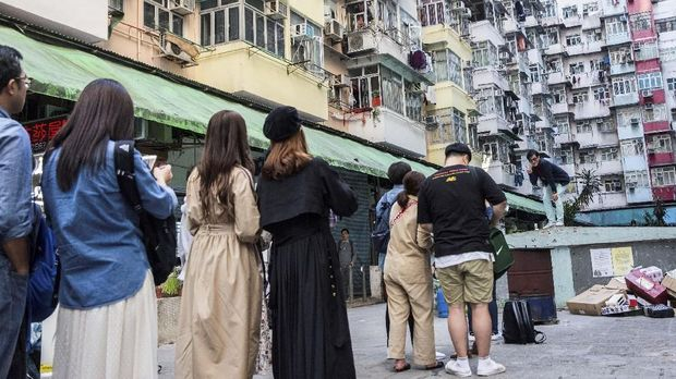 This picture taken on January 20, 2019 shows people (L) lining up to take a photo at a popular Instagram spot in Hong Kong. - For smartphone-wielding hordes of tourists, Hong Kong boasts a host of must-have Instagram locations -- but crowds of snap-happy travellers are testing local patience and transforming once quaint pockets of the bustling metropolis. (Photo by Isaac LAWRENCE / AFP) / TO GO WITH HongKong-lifestyle-tourism-photography, FEATURE by Elaine YU