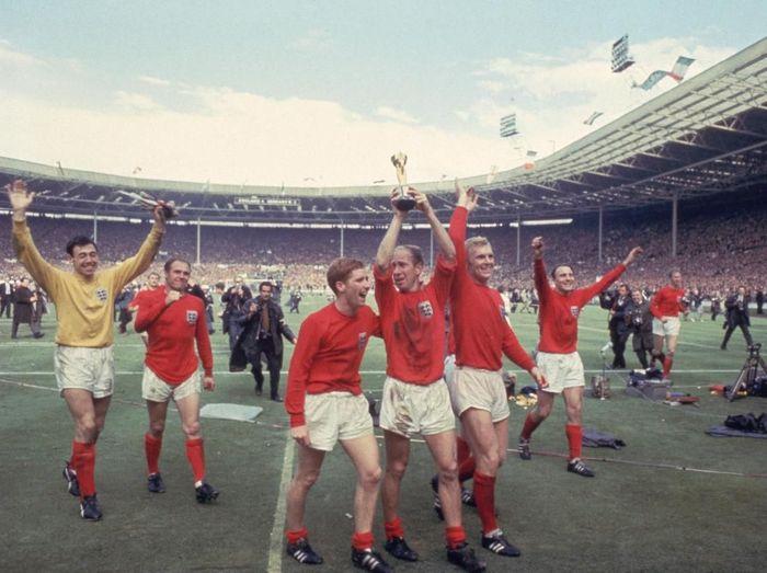 Bobby Charlton mengangkat trofi Jules Rimet 1966 bersama penggawa Timnas Inggris dan Gordon Banks mengikuti di belakang (Hulton Archive/Getty Images)