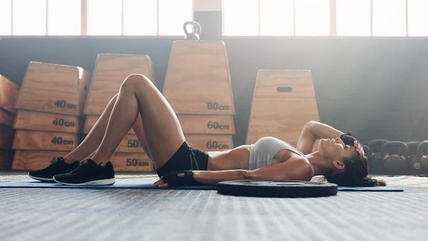 Young woman lying on her back at the gym after her workout. Fitness woman relaxing after exercise session.