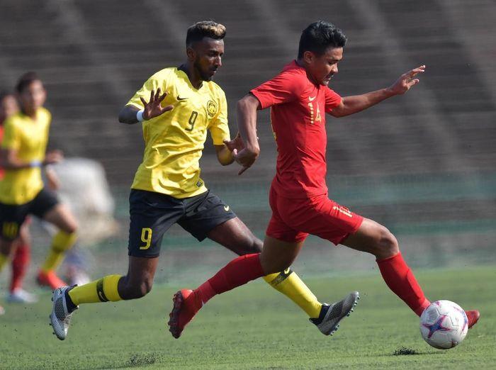 Pemain Timnas U-22 Indonesia Asnawi Mangkualam Bahar (kanan) berebut bola dengan pemain Malaysia Thivandaran Kaman dalam pertandingan Grup B Piala AFF U-22 di Stadion Nasional Olimpiade Phnom Penh, Kamboja, Rabu (20/2/2019). ANTARA FOTO/Nyoman Budhiana/aww.